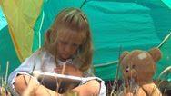 Stock Video Footage of Child, Girl Playing on Tablet, Ipad by Tent in Mountains, Camping, Kids in Trip