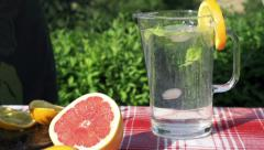 Woman throwing ice cubes into the jug of water, slow motion shot at 240fps Stock Footage