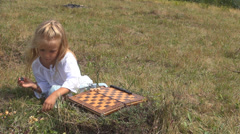 Child, Girl Playing Backgammon on a Chessboard on Meadow, Checkers, Draughts Stock Footage