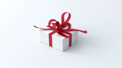 White, low gift box with red ribbon opening Stock Footage