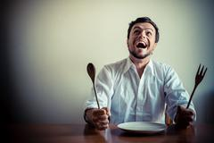 young stylish man with white shirt eating in mealtimes - stock photo