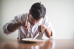 young stylish man with white shirt eating carrot - stock photo