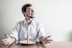 Young stylish man with white shirt eating carrot Stock Photos