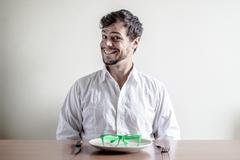 Young stylish man with white shirt eating green eyeglasses Stock Photos