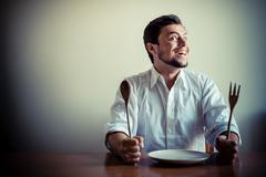 Young stylish man with white shirt eating in mealtimes Stock Photos