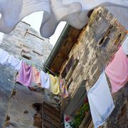 Colored laundry hanging out on a clothesline in the street Stock Photos