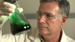 Scientist shaking green fluid in beaker Stock Footage
