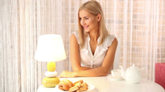 Pretty girl sitting at table at cafe looking at camera and smiling. Panning Stock Footage