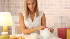 Cute girl sitting at table at cafe pouring tea into cup looking at camera and Stock Footage