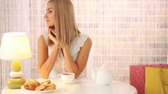 Charming girl sitting at table at cafe drinking tea and smiling. Panning camera Stock Footage