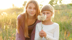 Two Cute Girls Blowing Dandelion, Happy Kids Having Fun in Summer Nature HD - stock footage