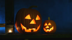 Two glowing jack-o-lanterns and a candle sit on a porch with eerie smoke - stock footage