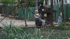 Happy baby boy play with water from a big spot in rural courtyard Stock Footage