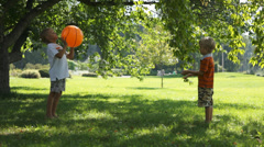 Two boys playing with a ball in the garden - stock footage