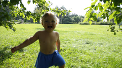 Happy baby in garden laughs out loud - stock footage