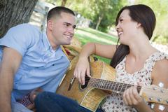 happy mixed race couple at the park playing guitar and singing songs. - stock photo