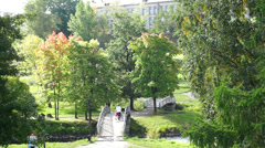 Mother walking with kid in a park near river Stock Footage
