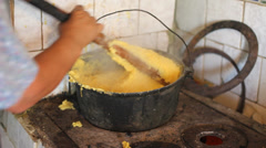 Woman hands prepare traditional food polenta on old stove Stock Footage