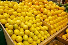 wooden bins filled with fresh lemons and oranges - stock photo