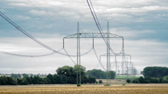 Electrical pylons with time-lapsed cloudy sky Stock Footage
