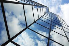 Reflecting clouds in glass facade Stock Photos