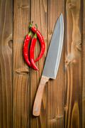 chili peppers with sharp knife - stock photo