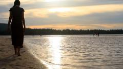 A woman walking on the beach during sunset. Stock Footage