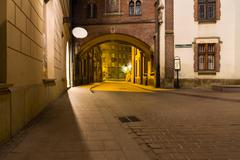 mysterious narrow alley with lanterns in krakow at night - stock photo