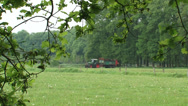 Farmer rides on tractor with manure trailer in small scaled landscape Stock Footage
