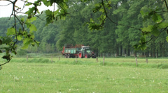 Farmer on tractor spreading organic manure in small scaled landscape + zoom out Stock Footage