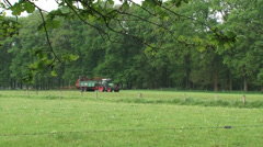 Armer on tractor spreading organic manure in small scaled landscape Stock Footage