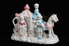 Ceramic figurine in the form of carriage drawn by two horses and three people Stock Photos