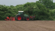 Farmer sowing a ploughed a small scaled field with tractor  - tracking shot Stock Footage