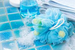 Soft blue bath puff or sponge  on blue tile  background Stock Photos