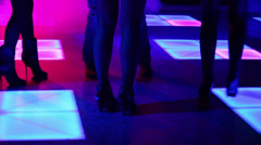 Three women and one man dance in night club Stock Footage