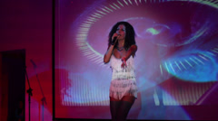 Young woman in dress with fringe sings near screen at night club Stock Footage