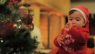Stock Video Footage of A little baby Santa Claus at a lighted Christmas tree 3