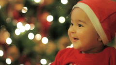A little baby Santa Claus at a lighted Christmas tree 5 Stock Footage