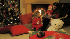 A mother reads Christmas stories to their children Stock Footage