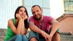 Happy couple sitting on stairs and chatting HD Stock Footage