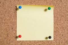 Yellow memo stick on cork board background Stock Photos