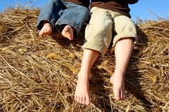Feet of little boys sitting on top of hay bale Stock Photos