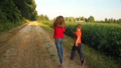 Young kids skipping down country road Stock Footage