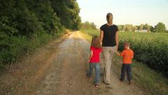 Mom and kids walking down a path Stock Footage
