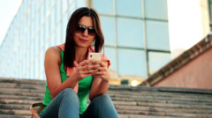 Young woman sending sms, texting on smartphone in the city HD Stock Footage