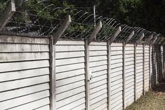 Precast concrete wall with razor sharp barbed security wire Stock Photos