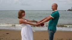 Happy pregnant woman and her husband on the seacoast. Stock Footage