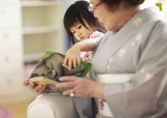 Grandmother and granddaughter reading a picture book - stock photo