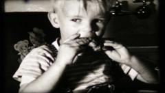513 - blonde haired boy eats chicken leg at home - vintage film home movie Stock Footage