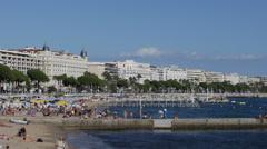 View French Riviera People Sunbathe Sunbathing Swimming Beach Umbrella Cannes Stock Footage